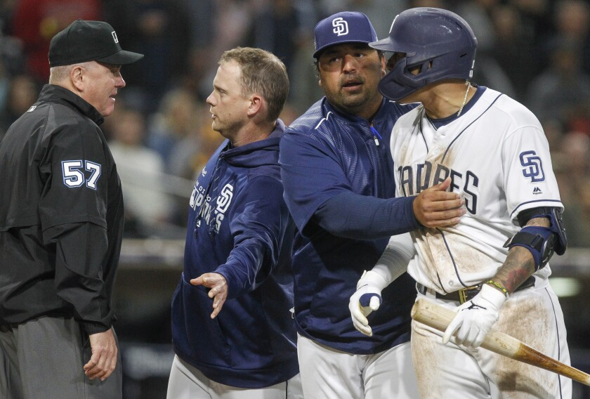 Padres bench coach Rod Barajas moves Manny Machado away as manager Andy Green talks to third base umpire Mike Everitt after home plate umpire Bill Welke ejected Green during the sixth inning.
