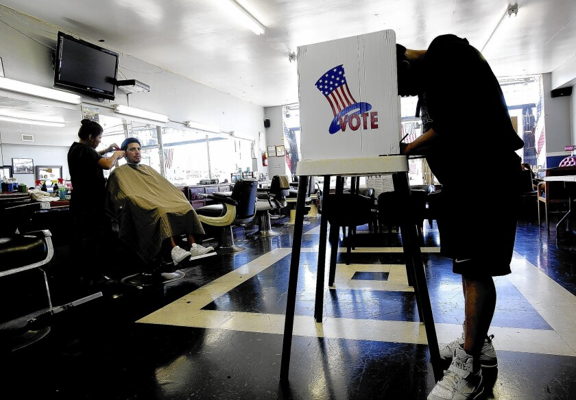 Lasbia Batista, left, gives a haircut to Jose Bejarano as Marco Garcia casts his ballot during election day at Utah's Barber Shop in Long Beach.
