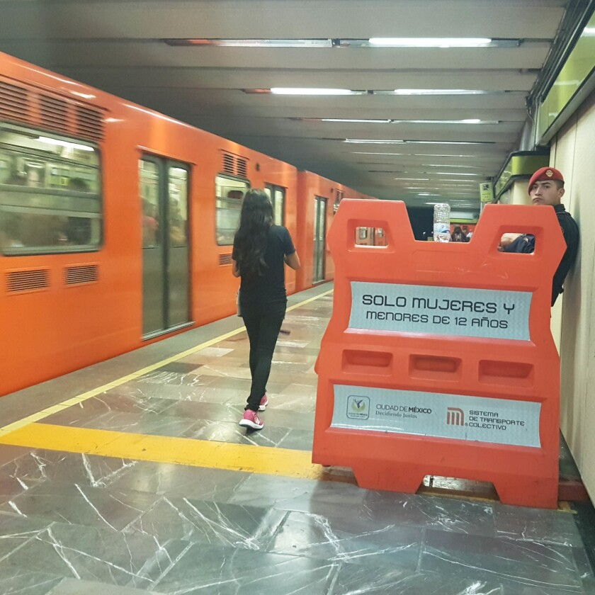 A woman walks toward the area designated for women and children only in a Mexico City subway station.