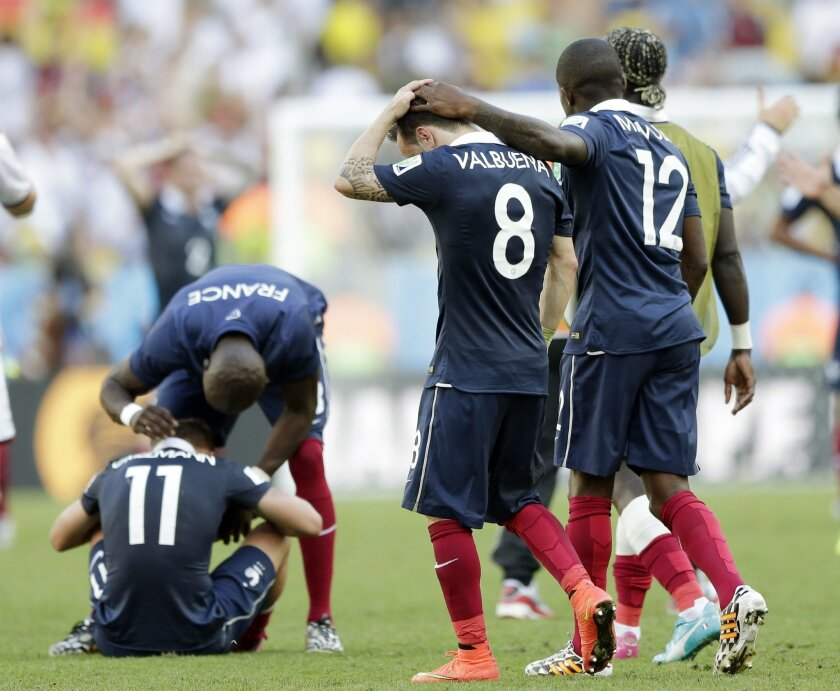 France's Rio Mavuba walks off the pitch with his teammate Mathieu Valbuena (8) after Germany defeated France 1-0 to advance to the semifinals during the World Cup quarterfinal soccer match at the Maracana Stadium in Rio de Janeiro, Brazil, Friday, July 4, 2014. Left is France's Eliaquim Mangala and Antoine Griezmann. (AP Photo/Matthias Schrader)