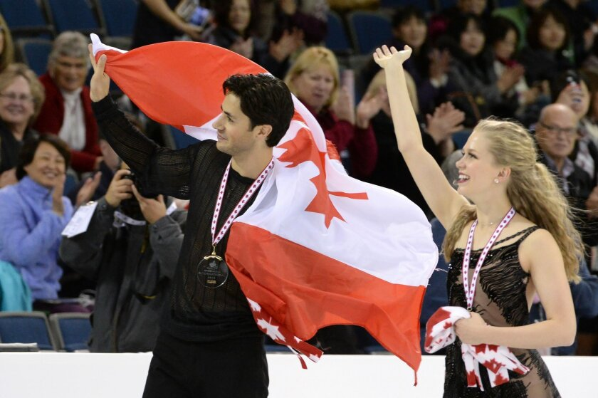 Andrew Poje and Kaitlyn Weaver, of Canada, celebrate their gold-medal win in the ice dance free dance at the Skate Canada International figure skating competition in Lethbridge, Alberta, Saturday, Oct. 31, 2015. (Jonathan Hayward/The Canadian Press via AP) MANDATORY CREDIT