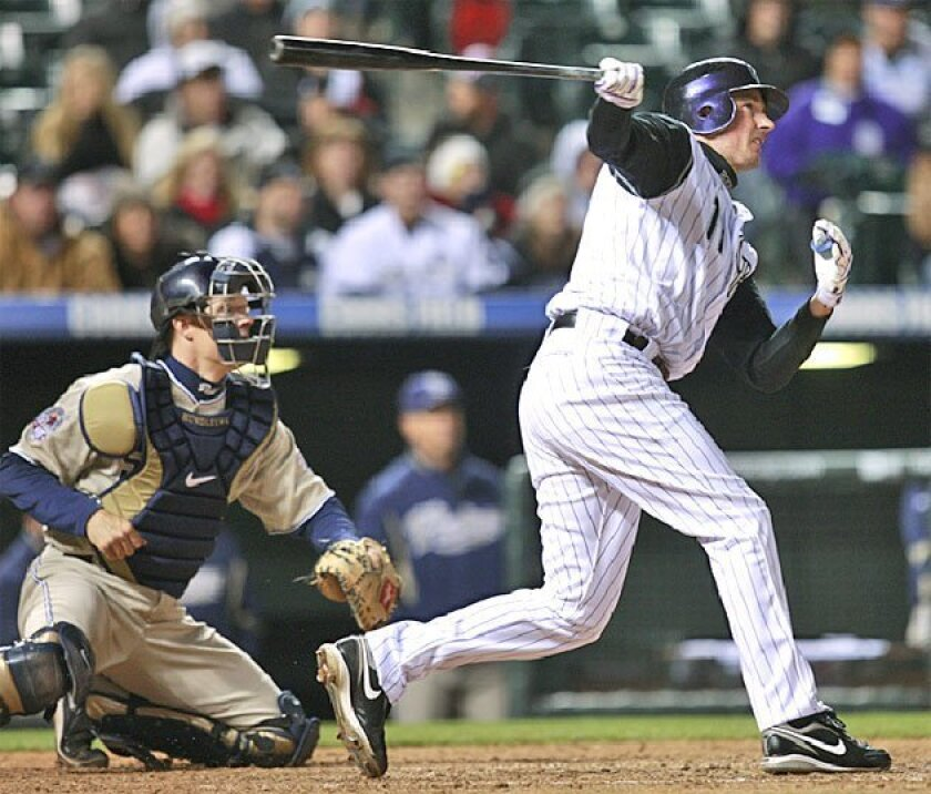The Rockies' Brad Hawpe hits a two-run triple in the fourth inning to help beat the Padres in a 2009 game. (Associated Press)