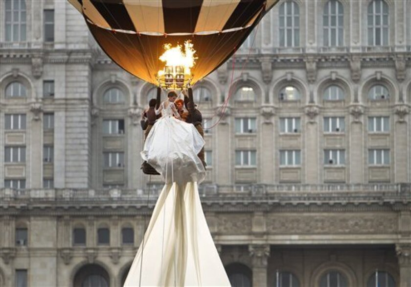 A model rides in a hot air balloon to show the worlds longest wedding dress train during a Guinness World Record attempt in Bucharest, Romania, Tuesday, March 20, 1012.  Romania has set the world record for the world's longest bridal train.  The nearly 3-kilometer (1.86-mile) long ivory train, whic