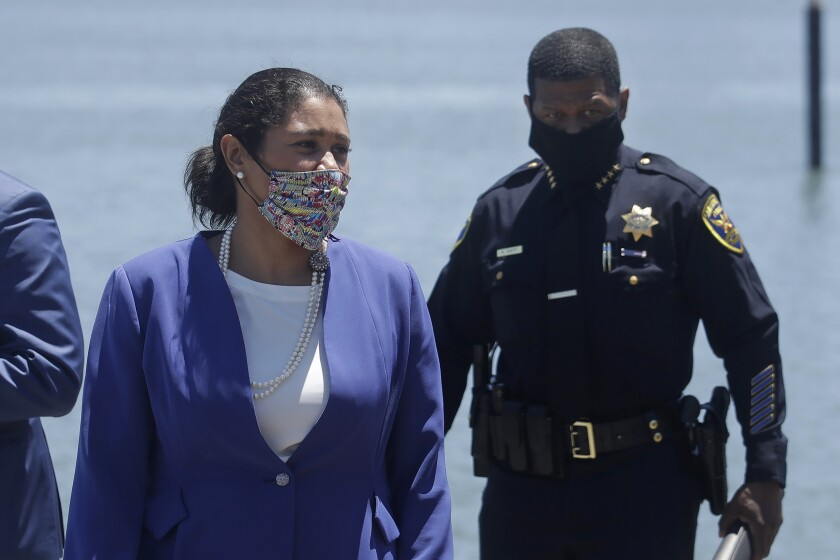 FILE - In this July 7, 2020, file photo, Mayor London Breed, center, and San Francisco Police Chief William Scott, right, arrive at a news conference in San Francisco. Breed and Scott say they'll dedicate more police, beef up coordination and make it easier for retailers to report shoplifters. Brazen commercial thieving caught on video has added to the city's reputation as a lawless land of crime. (AP Photo/Jeff Chiu, File)