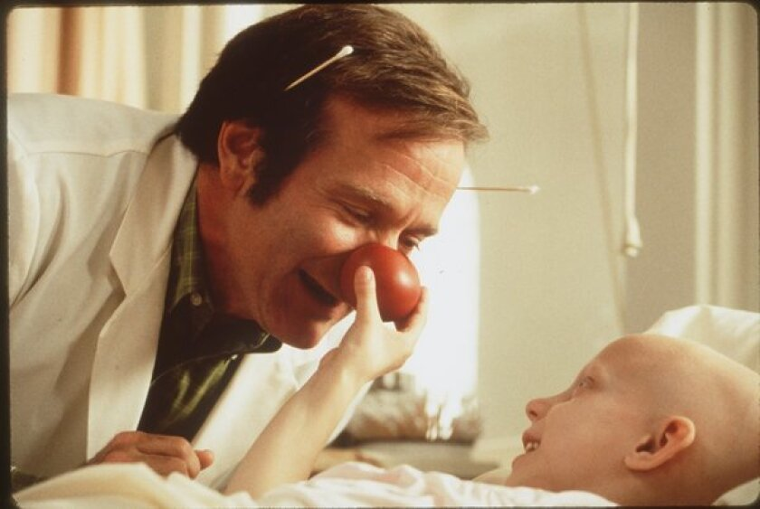 """German researchers are probing different areas of the brain that respond to laughter. In this photo, Robin Williams plays a doctor who makes patients laugh in the film """"Patch Adams."""""""