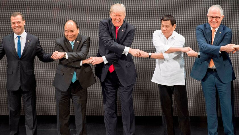 President Trump joins hands with, from left, Russian Prime Minister Dmitry Medvedev, Vietnamese Prime Minister Nguyen Xuan Phuc, Philippine President Rodrigo Duterte and Australian Prime Minister Malcolm Turnbull for the group photo opening the ASEAN summit in Manila.