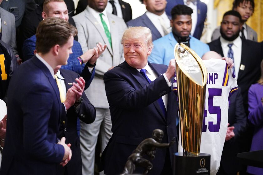 "A smiling President Trump holds up a ""Trump 45"" LSU football jersey during the team's visit to the White House."