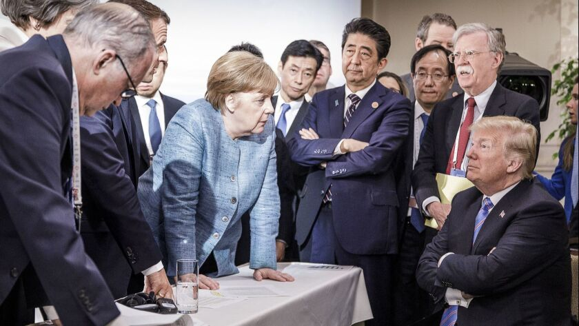 German Chancellor Angela Merkel deliberates with President Trump on the sidelines of the official agenda during the Group of 7 summit on June 9, 2018, in Charlevoix, Canada.