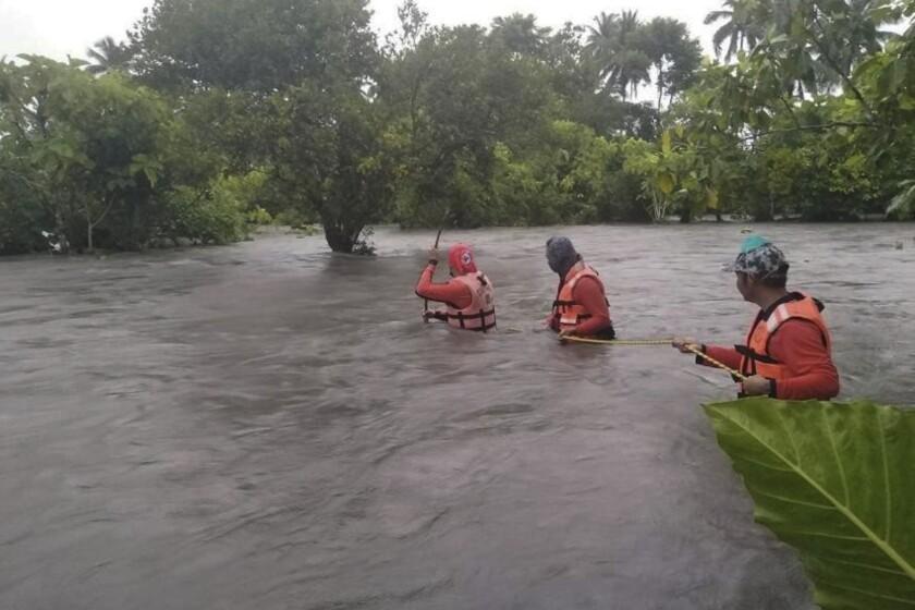 Fotografía proporcionada por la Guardia Costera de Filipinas de sus miembros atravesando áreas inundadas mientras buscan a residentes para llevarlos a lugares más seguros en Naujan, Filipinas, el viernes 23 de julio de 2021. (Philippine Coast Guard vía AP)