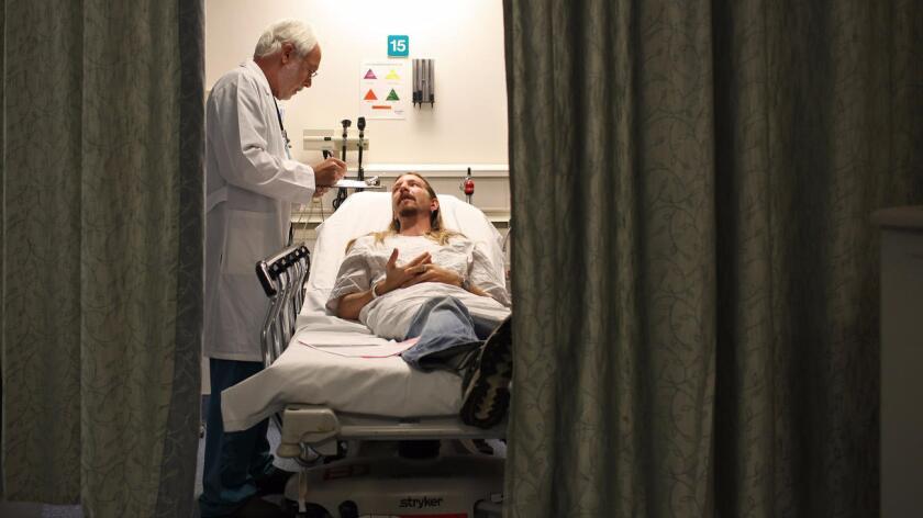 Un doctor examina a un paciente en el Centro Médico St. Joseph en Burbank. Los Angeles Times.