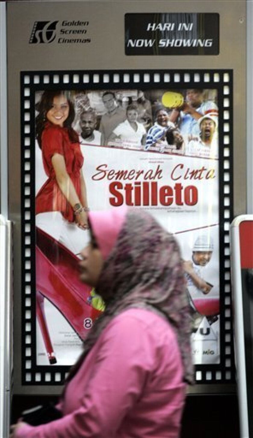 A Muslim woman walks past a Malay movie poster at a cinema in Kuala Lumpur, Malaysia, Thursday, April 8, 2010. Malaysia's first gay-themed movie could hit cinemas within months, its producer said, after government censors eased restrictions that have stifled the film industry here for decades. (AP Photo/Lai Seng Sin)