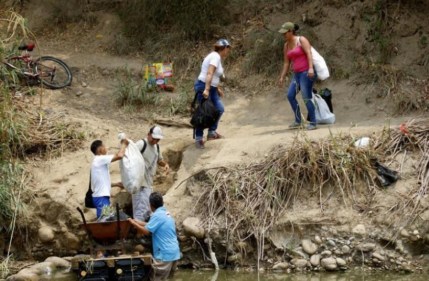 "Venezuelans on March 6, 2019, make their way across the Colombia-Venezuela border via a ""trocha,"" an illegal trail normally used by smugglers and drug traffickers. EPA-EFE/Schneyder Mendoza"