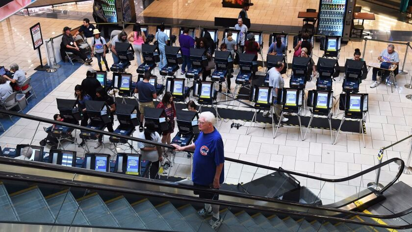 Voters casting ballots early in Las Vegas. Early voting in Nevada is up from four years ago, an expert says.