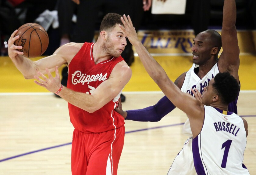 Clippers forward Blake Griffin makes a pass over Lakers guards Kobe Bryant and D'Angelo Russell during the first half on Dec. 25.