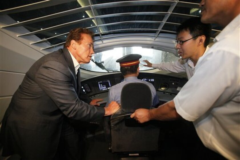 California Gov. Arnold Schwarzenegger, left, is briefed as he tours China's high-speed train  at Hongqiao Railway Station in Shanghai, China Sunday, Sept. 12, 2010. Schwarzenegger is riding the rails, China's new high speed train lines, engaging in a little window shopping while peddling California