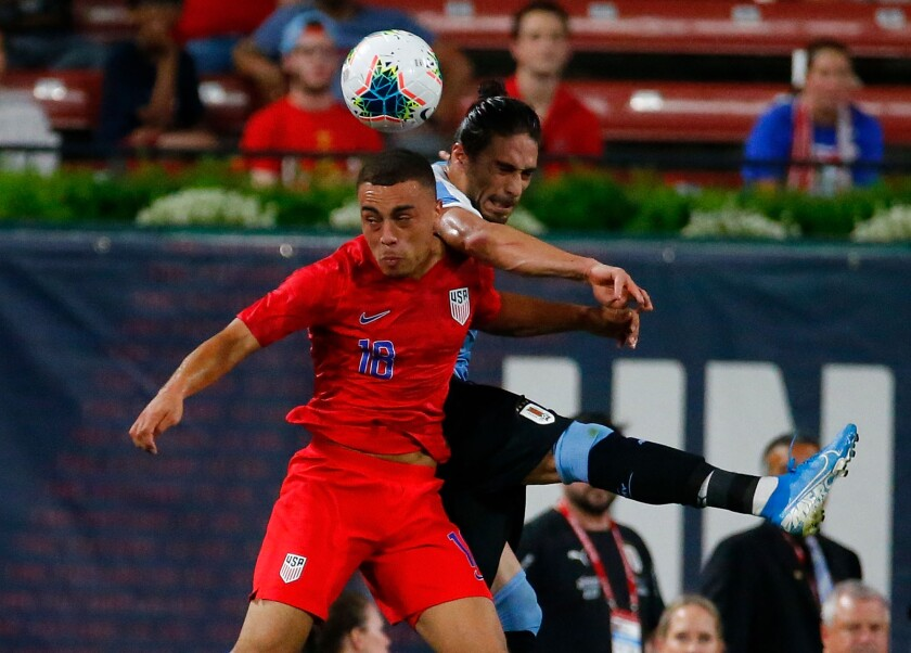 U.S. defender Sergiño Dest, front, heads the ball in front of Uruguay's Martín Caceres.