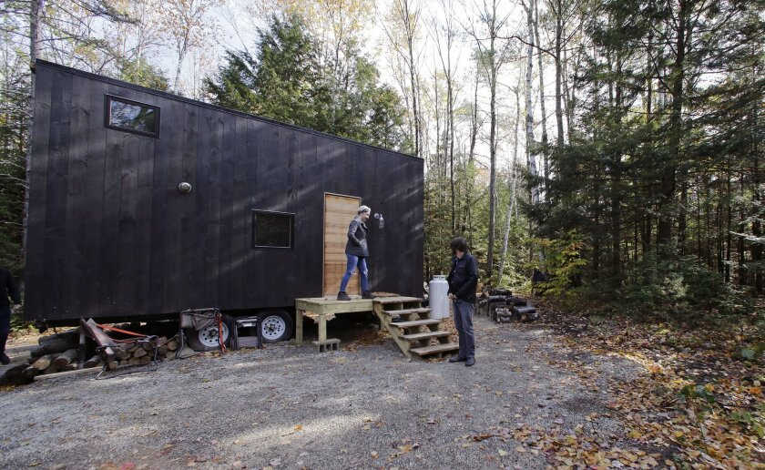 In this Tuesday, Oct. 20, 2015 photo, Hilary Lentz, of Pittsburgh, Pa., and her husband Shane leave the tiny house which they rented for a weekend in Croydon, N.H. As the tiny house phenomenon sweeps the nation, Harvard's Millennial Housing Lab thinks a tryout is in order for people toying with rad