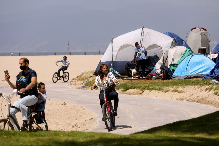 Cyclists pass  tents along the bike path in Venice