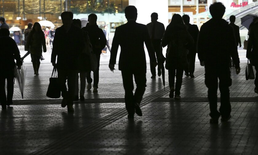 People walk on a street in Tokyo Monday, Feb. 15, 2016. Japan's economy contracted at a 1.4 percent annual pace in the last quarter, October-December in 2015, as weak consumer demand and slower exports battered the recovery. The preliminary data, which may be revised, were slightly worse than expec