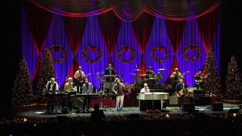 Beach Boys co-founder Brian Wilson, at the piano, sings hits from the Beach Boys' 1964 Christmas album with his band at the Fred Kavli Theatre on Thursday in Thousand Oaks.
