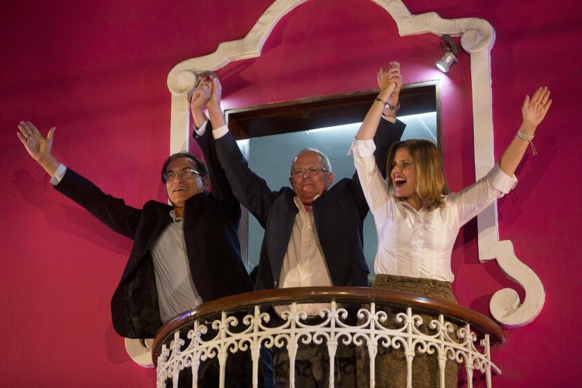 Presidential candidate Pedro Pablo Kuczynski, center, celebrates with his running mates for first and second vice-presidents Martin Vizcarra, left, and Mercedes Araoz, right, from the balcony of their headquarters in Lima, Peru, Sunday, June 5, 2016. Early exit polls show presidential candidate Ped