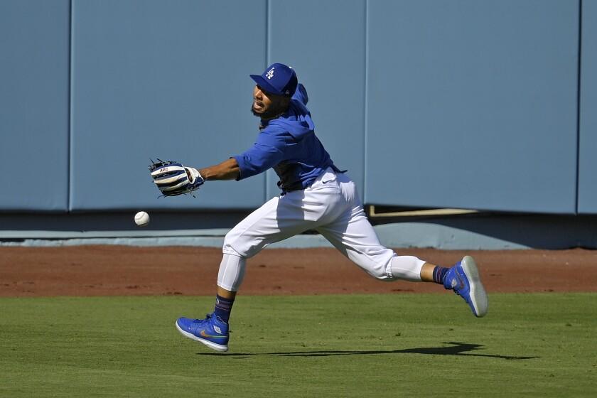 Mookie Betts de los Dodgers de Los Ángeles trata de atrapar una pelota
