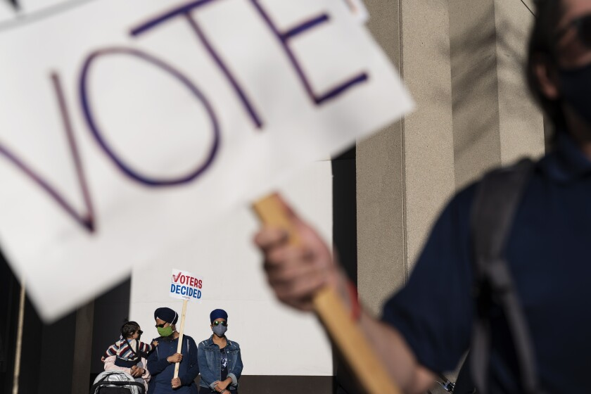 """Demonstrators hold a sign saying """"Voters decided"""" in Detroit on Nov. 7 as they celebrate the election results."""