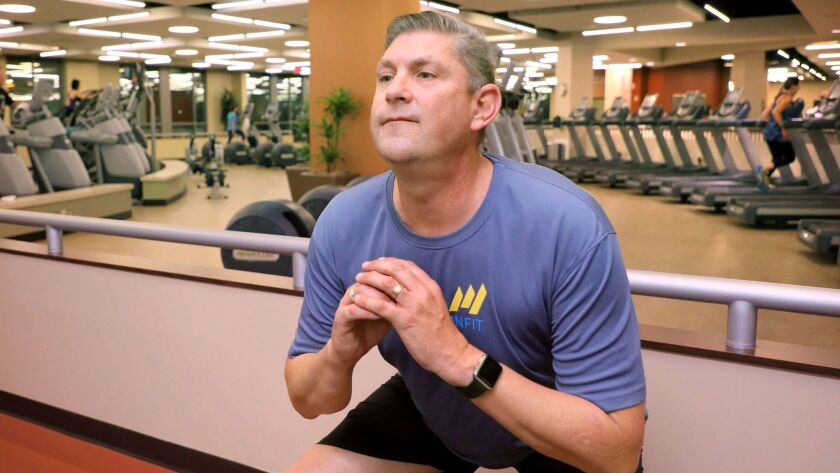 """Cancer survivor Keith Stuessi, 50, stretches during an evening workout with Tri-City Medical Center's """"Lucky 13"""" at the Tri-City Wellness Center."""