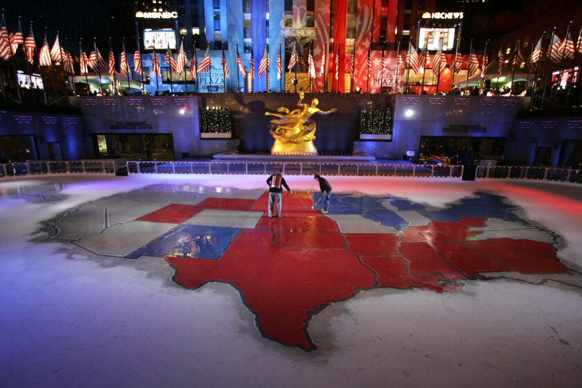 Workers stand on a gargantuan electoral map of the U.S. in the ice rink at Rockefeller Center.