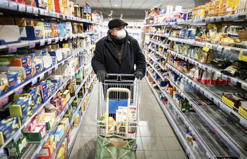 A customer wearing a face mask and gloves goes shopping in the early morning in a supermarket in the Berlin district of Friedenau, Germany, Tuesday, March 17, 2020 In order to slow down the spread of the coronavirus, the German government has considerably restricted public life. Only for most people, the new coronavirus causes only mild or moderate symptoms, such as fever and cough. For some, especially older adults and people with existing health problems, it can cause more severe illness, including pneumonia. (Kay Nietfeld/dpa via AP)