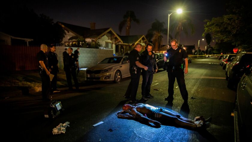 LAPD officers and detectives respond to a man shot dead in a car in South LA.