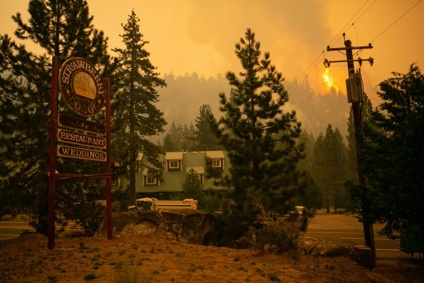 STRAWBERRY, CA - AUGUST 28: A spot fires burns on the ridge behind the historic Strawberry Lodge as firefighters continue to tackle the Caldor fire as it creeping closer to South Lake Tahoe on Saturday, Aug. 28, 2021 in Strawberry, CA. (Jason Armond / Los Angeles Times)