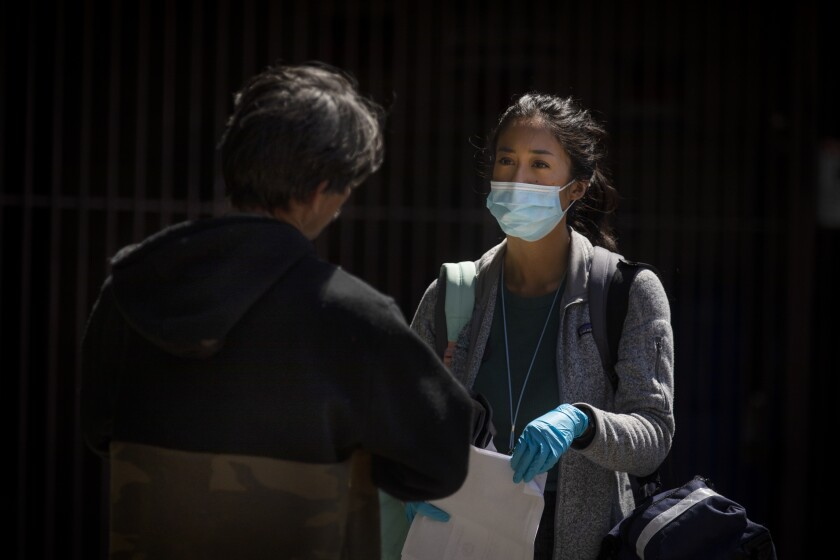 """Nurse practitioner Jen King, right, speaks with a man living in an encampment on a Los Angeles sidewalk. """"I feel like when you sign up for this job, you sign up to take certain risks and you have to treat people as safely as you can,"""" she said."""