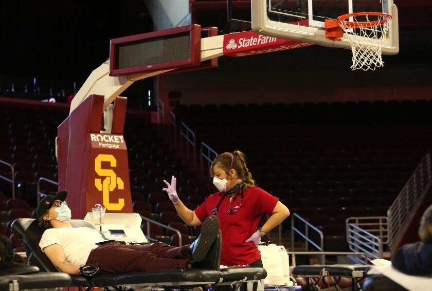 Alex Herron, left, under the care of nurse Mercy Pineda, participates in a blood drive April 14 at USC Galen Center.