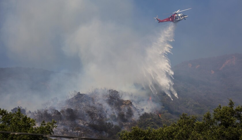 A Los Angeles Fire Department helicopter drops water on a brush fire near Topanga Canyon Boulevard north of Pacific Coast Highway in Malibu on Thursday afternoon.