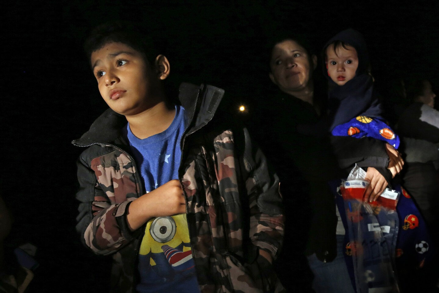 After crossing the Rio Grande River at night with the help of smugglers, women and children from Central America are detained by U.S. Border Patrol agents.