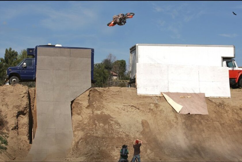 Larry Linkogle jumps between trucks in a stunt at his Temecula compound.