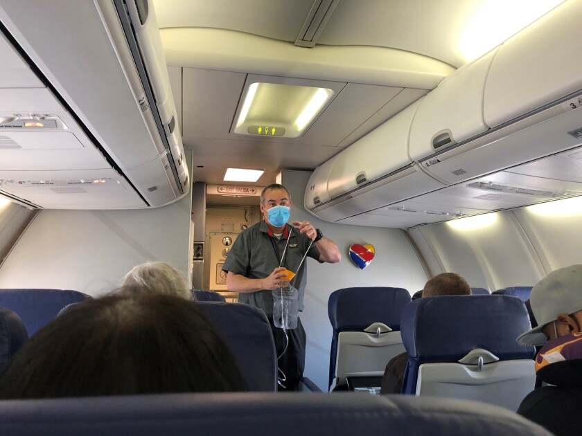 A flight attendant, wearing a mask, demonstrates the use of another at the outset.