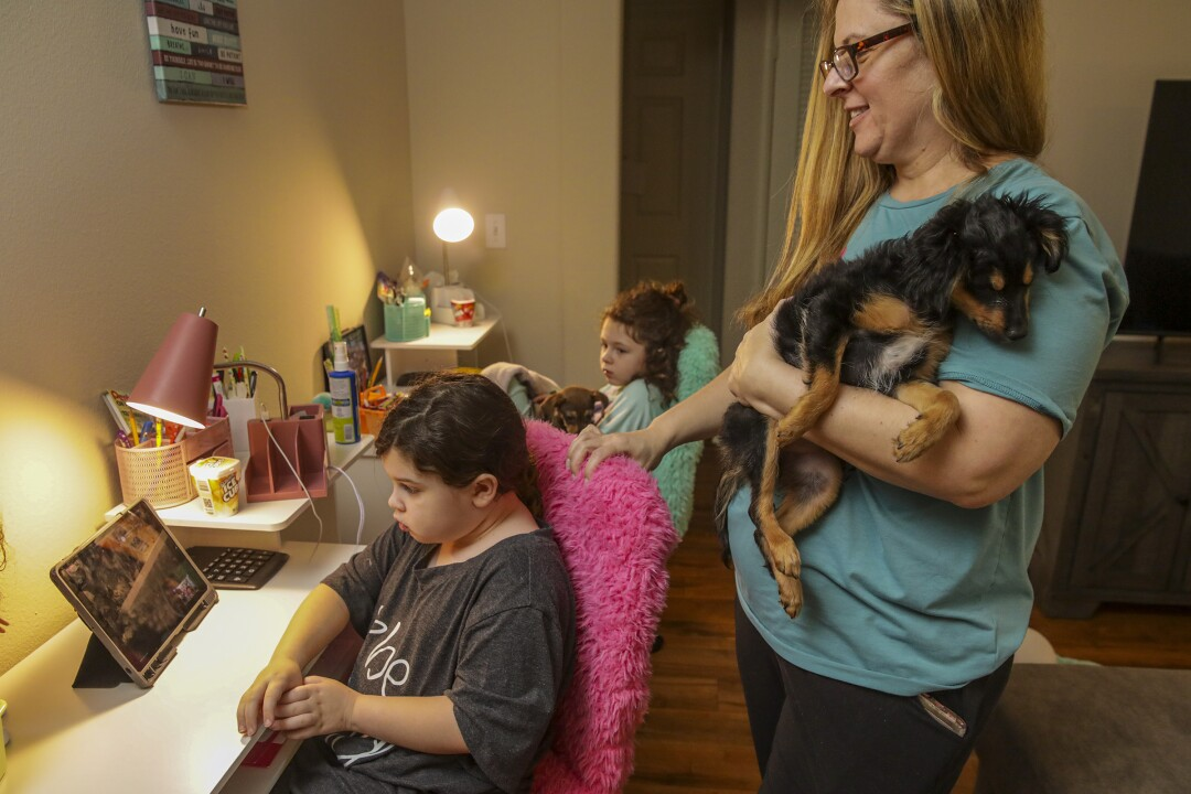 Alison Goldberg, holding support dog Zoey, watches her 7-year-old twins Savannah Singer, foreground, and Madelynn Singer.