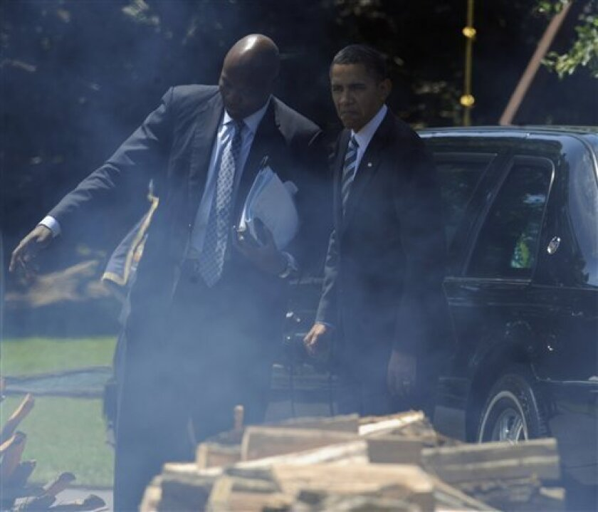 President Barack Obama, accompanied by personal aide Reggie Love, looks at the fire pit with on the South Lawn of the White House in Washington, Tuesday, June 8, 2010, after returning from a stop in Maryland. The President will host a Congressional BBQ later in the evening. (AP Photo/Susan Walsh)