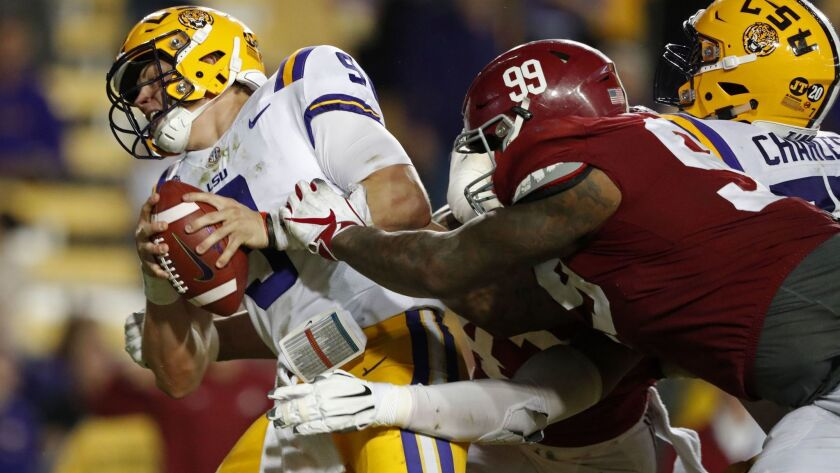 LSU quarterback Joe Burrow (9) tries to avoid a sack by Alabama defensive lineman Raekwon Davis (99) in the second half in Baton Rouge, La. on Nov. 3, 2018. Alabama won 29-0.