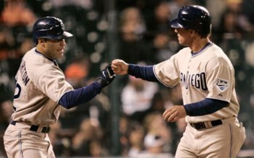 Padres' Scott Hairston, left, high-fives teammate Brian Giles after Giles scored on a bases-loaded bean ball by Giants reliever Billy Sadler in the 13th inning Friday in San Francisco. San Diego won 7-3. AP Photo/Marcio Jose Sanchez