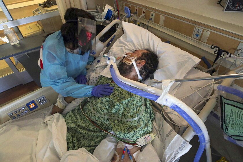 A man on a ventilator and a woman in personal protective equipment.