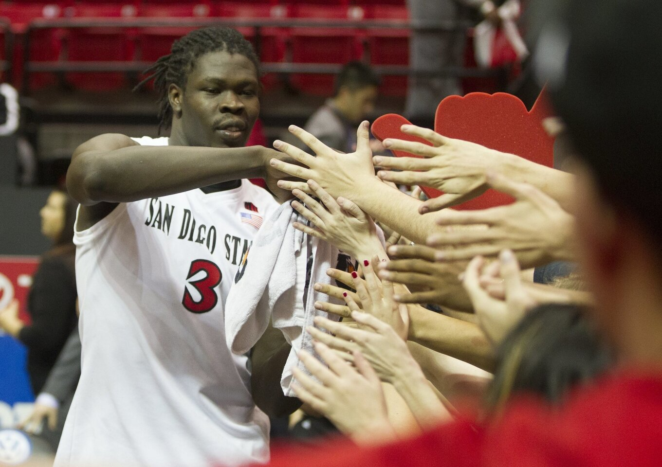 San Diego State vs Fresno State Mens Basketball at Viejas Arena.San Diego State Aztecs forward Angelo Chol (3) is congratulated by the students section after beating Fresno State.