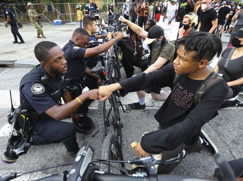 Atlanta Police Officer J. Coleman, left, and a protester fist bump in a symbolic gesture of solidarity.