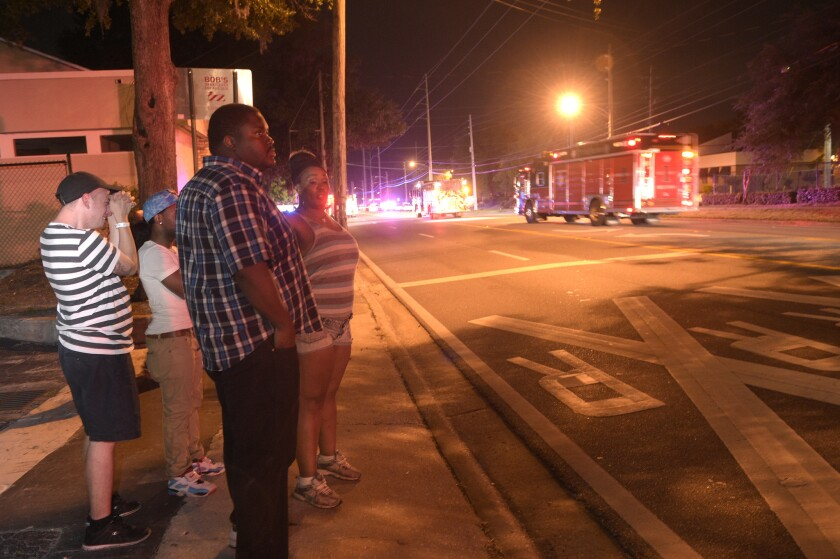 Bystanders wait down the street from a shooting involving multiple fatalities at the Pulse nightclub in Orlando, Fla. on June 12.