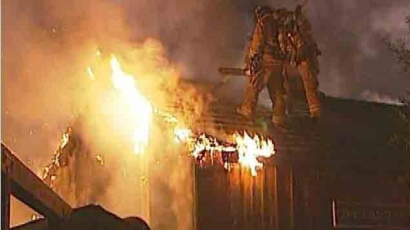 Firefighters attack the flames at El Patio de Old Town restaurant from the roof early Monday.
