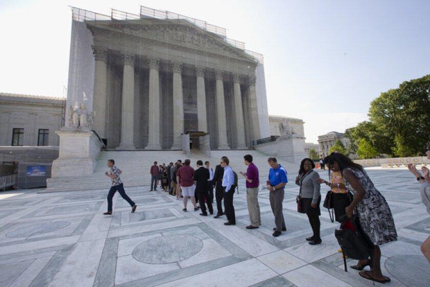 Visitors wait outside the Supreme Court in Washington on Thursday.