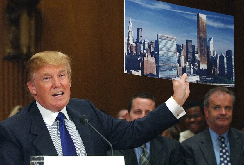 FILE - In this July 21, 2005, file photo, Donald Trump holds a picture of the New York City skyline while testifying on renovation of the United Nations Headquarters on Capitol Hill. When President Donald Trump visits the United Nations building in New York, he's not just thinking about the global challenges the world body faces, he's still got in mind the deal that got away. More than a decade later, Trump still relives the overtures he made to rebuild the 39-story tower in the early 2000s and posits that he could have done a better job of it. (AP Photo/Dennis Cook, file)