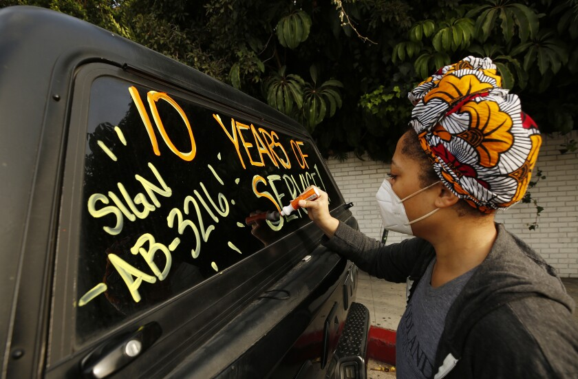 Courtney Banks writes on vehicle windows in support of workers who lost their jobs.
